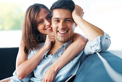 Buy stock photo Portrait of a beautiful young couple sitting together on couch at home - Indoor