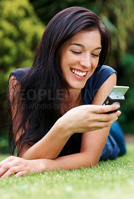 Buy stock photo Portrait of a beautiful young woman relaxing on grass and reading a funny sms on cellphone  - Outdoor