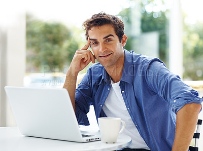 Buy stock photo Portrait of a young confident man sitting with a laptop and smiling