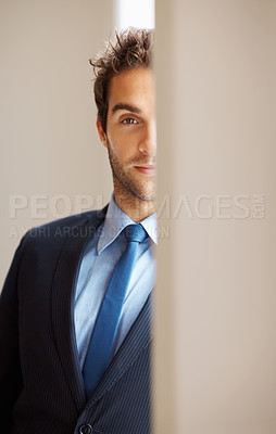 Buy stock photo Businessman hiding behind wall indoors