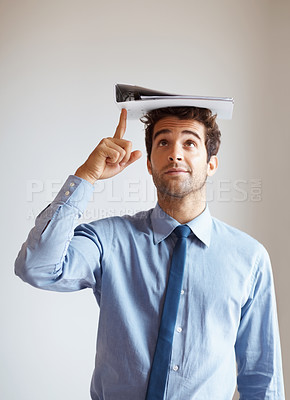 Buy stock photo Handsome executive smiling while pointing up at binder on head