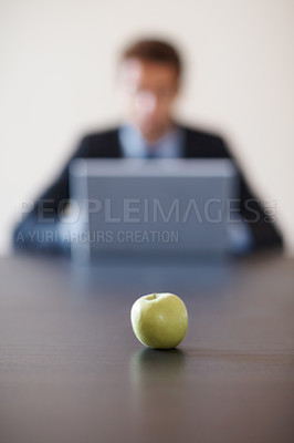 Buy stock photo Businessman working on laptop in background, focus on apple an apple on the desk in foreground - copyspace