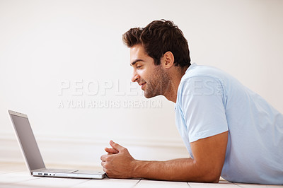Buy stock photo Side view of man lying on floor, looking at laptop