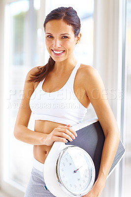 Buy stock photo Portrait of pretty young woman carrying a weighing scale and smiling
