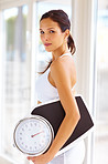 An attractive young woman holding weight scale