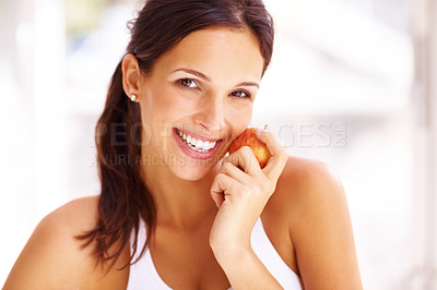 Buy stock photo Portrait of lovely young woman holding a fresh ripe apple and smiling