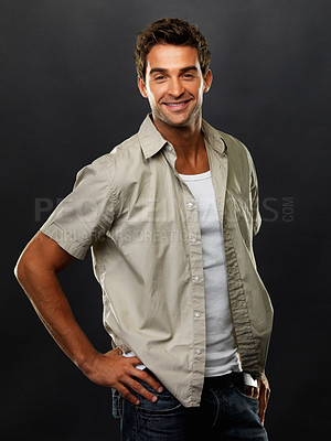 Buy stock photo Portrait of smart guy standing with hand on hip and smiling on black background
