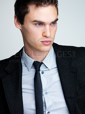 Buy stock photo Closeup portrait of a young male business executive lost in deep thought against grey background