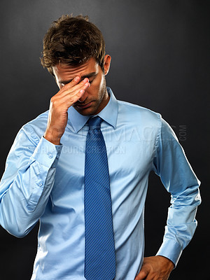 Buy stock photo Tired business man holding his head and looking down on black background