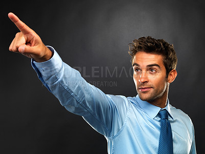 Buy stock photo Young business man standing on black background and pointing away