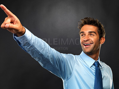 Buy stock photo Business man smiling and pointing away on black background