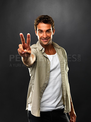 Buy stock photo Portrait of man smiling and showing a victory sign on black background