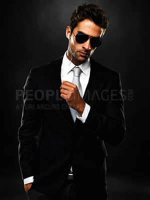 Buy stock photo Portrait of a sexy secret service employee in a sharp suit with an ear-piece and shades, against a shadowy background