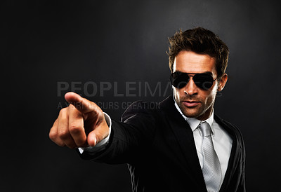 Buy stock photo Secret service employee standing on black background and pointing at someone