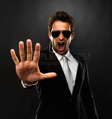 Buy stock photo Secret agent standing on black background holding out his palm and screaming to stop