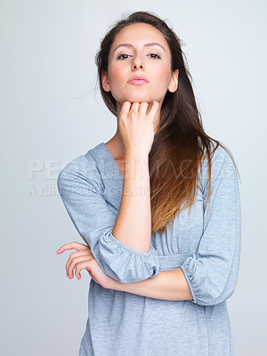 Buy stock photo Portrait of an attractive young woman posing confidently against grey background