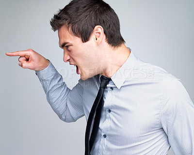 Buy stock photo Portrait of an angry young business man pointing at against grey background