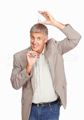 Buy stock photo Studio shot of a mature man holding a lightbulb over his head against a white background