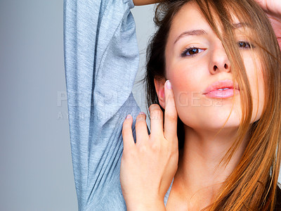 Buy stock photo Closeup portrait of a beautiful young female model posing against grey background