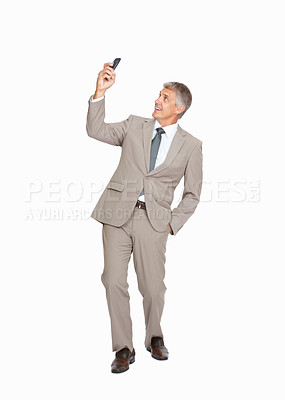 Buy stock photo Studio shot of a mature businessman taking a selfie with his mobile phone against a white background