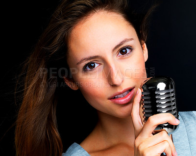 Buy stock photo Closeup portrait of a successful young female jazz singer holding old fashioned microphone