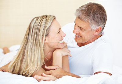Buy stock photo Portrait of romantic mature couple looking at each other while lying on bed