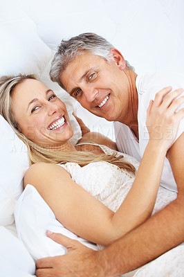 Buy stock photo Portrait of romantic couple hugging each other and lying together in bed at home