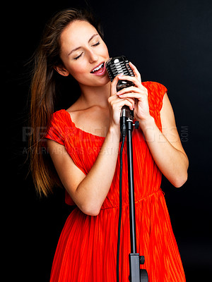 Buy stock photo Portrait of a happy young female jazz singer singing with an old fashioned microphone