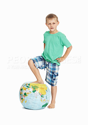 Buy stock photo Full length of a young boy with his foot on the globe on white background