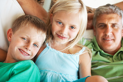 Buy stock photo Portrait of young boy and girl looking at you with their father in background