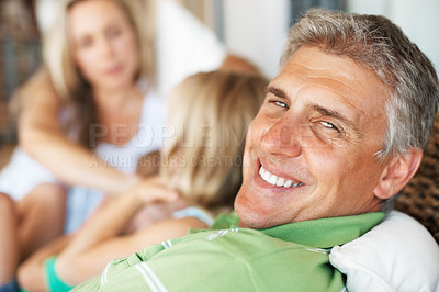 Buy stock photo Closeup of smiling handsome mature man with his family in background