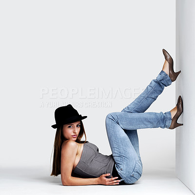 Buy stock photo Portrait of a pretty young woman posing while lying on the floor against grey background