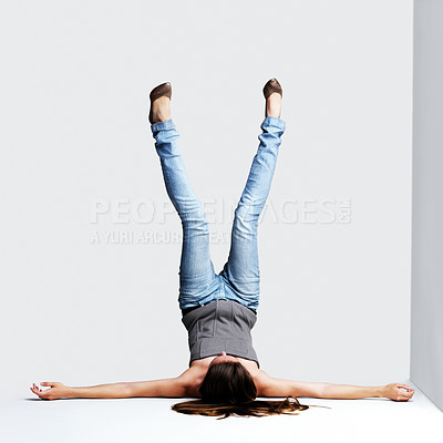 Buy stock photo Portrait of a young woman lying in upside down posture against grey background