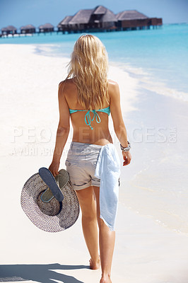 Buy stock photo Rear view of a sexy young lady walking through the beach towards the house