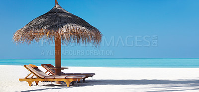 Buy stock photo An attractive view of a beach with chairs and umbrella