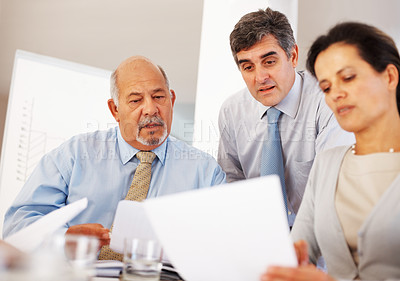 Buy stock photo Three confident people reading business document together in the office