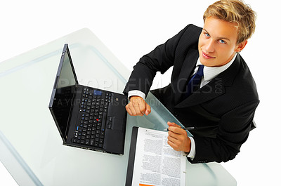 Buy stock photo High angle studio shot of a young businessman sitting at his desk isolated on white