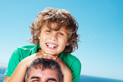 Buy stock photo Closeup portrait of little boy sitting of father against clear blue sky