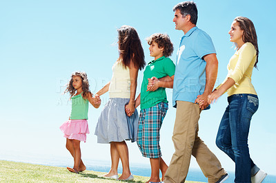 Buy stock photo Portrait of family holding hands and walking in row against clear blue sky