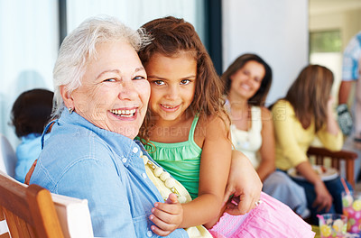 Buy stock photo Grandmother hugging granddaughter with family in background