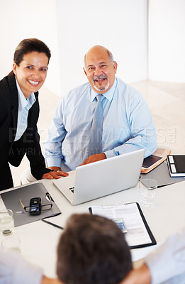 Buy stock photo Successful business executives sitting in front of relaxed colleague