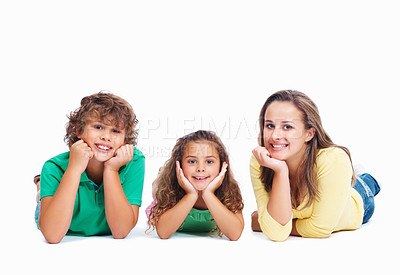 Buy stock photo Portrait of happy little children lying on studio floor with copyspace