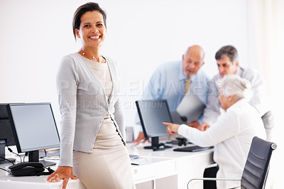 Buy stock photo Smiling businesswoman while her colleagues have a discussion in the background