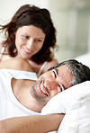 Happy man lying on bed with his wife in background