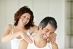 Attractive woman giving shoulder massage to her husband