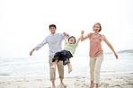 Excited young family playing on the sea shore