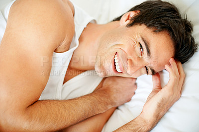 Cheerful young guy waking up in morning on bed