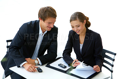 Buy stock photo Shot of a two businesspeople sitting a table talking together over paperwork
