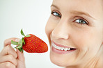 Closeup of a happy female eating a strawberry