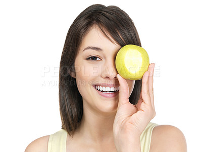Buy stock photo Closeup portrait of a cute young female holding a green apple over eye